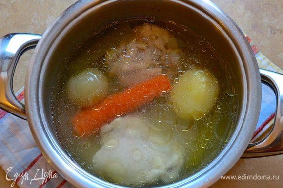 Первым делом приготовить бульон. Для этого в кастрюлю положить куриные бедрышки, очищенные овощи, залить достаточным количеством воды и поставить вариться на полтора часа.