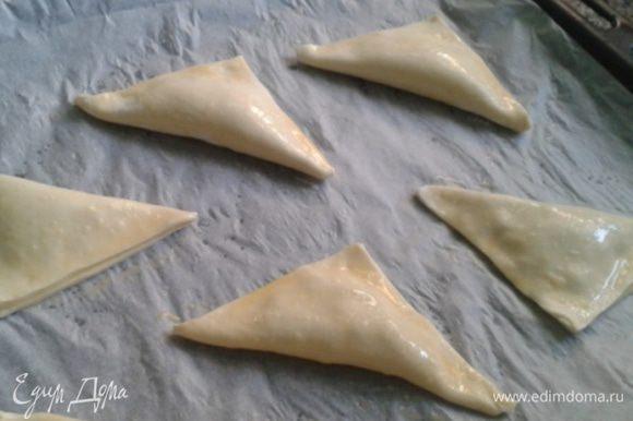 Сложить по диагонали в треугольник и слегка придавить по краю. Заготовки поместить на 15 минут в холодильник. Охлажденные треугольники смазать яичной болтушкой и отправить в горячую духовку.