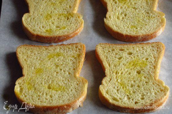 Ломтики хлеба сбрызнуть оливковым маслом, выложить на противень с пергаментом и запечь в разогретой до 180 С духовке 6 минут.