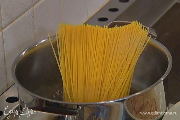 Спагетти целиком опустить в кипящую соленую воду и варить на 1–2 минуты меньше, чем указано в инструкции на упаковке, затем воду слить и сохранить.
