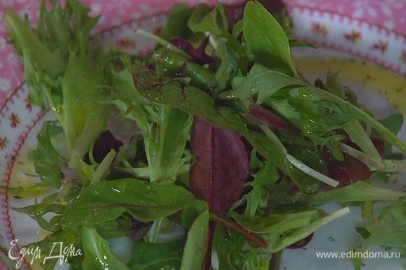 Салатные листья выложить на тарелку, сбрызнуть оливковым маслом, соком лимона, посолить и поперчить.