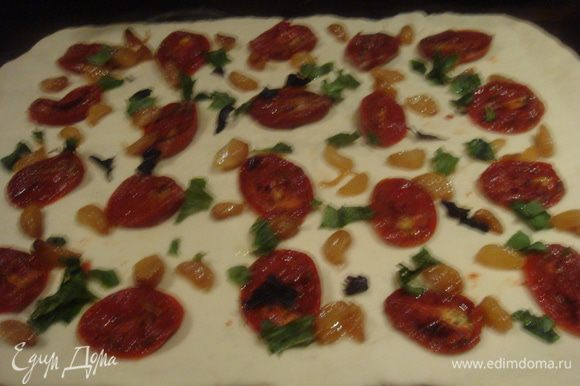 Выложить тесто на посыпанную мукой рабочую поверхность. Раскатать в прямоугольник. На тесто выложить помидоры, печеный чеснок и базилик.