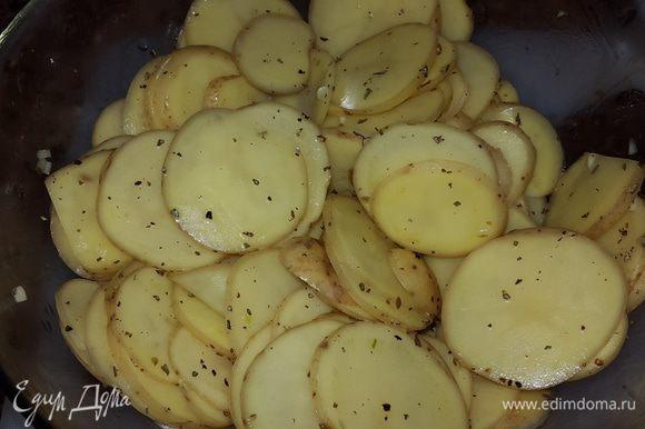 Картофель выкладываем в глубокую миску, солим, перчим, добавляем травы, чеснок, немного масла от вяленых томатов и перемешиваем руками.