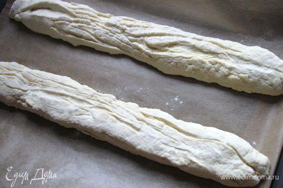 Духовку разогреть до 250С вместе с дополнительным противнем, в который будете наливать воду, когда поставите хлеб. Перевернуть тесто и перенести на лист бумаги для выпечки на противень, одновременно растягивая до максимально возможной длины (длина противня). Чуть присыпать мукой.