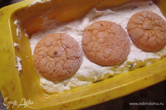 Возьмите силиконовую форму, смажьте ее растительным маслом и выложите в нее половину творожной массы. Печенье склейте с помощью джема и выложите поверх творожной массы в форму. Оставшиеся промежутки можно тоже заполнить джемом.