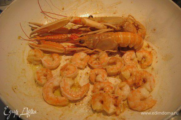 В отдельной сковороде на сильном огне обжарить на оливковом масле с зубчиком чеснока креветки и лангустины. Посолить, поперчить красным острым перцем.