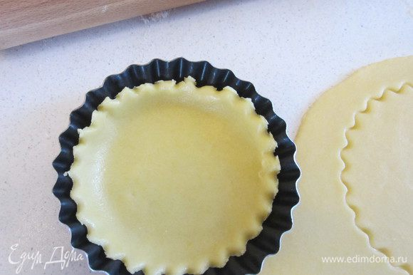 Тем временем раскатываем тесто, вырезаем кружочки, раскладываем тесто по формочкам.