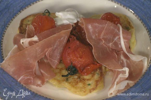 Готовые оладушки подавать с запеченными помидорами, ветчиной, сметаной и аджикой.