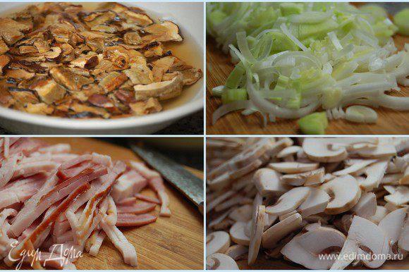 Сушеные грибы залить 1,5 стакана кипятка и оставить на 30 минут. Белую часть порея нарезать полукольцами, шампиньоны – тонкими пластинками, бекон – соломкой.