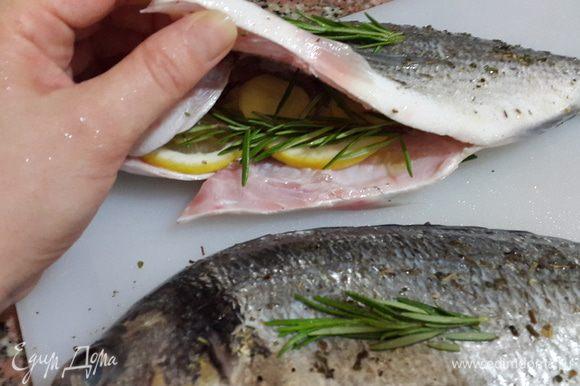 В брюшко каждой рыбины вложила дольки лимона, имбирь и нижнюю часть веточки розмарина. Верхнюю часть веточки выложила на рыбу сверху.
