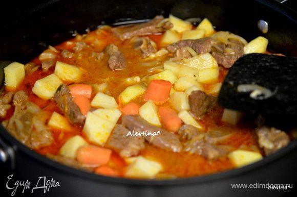 Через пройденный час добавить в общее блюдо, переложить морковь и лук, очищенный и порезанный кубиками картофель. Закрыть крышкой и тушить 30 мин.