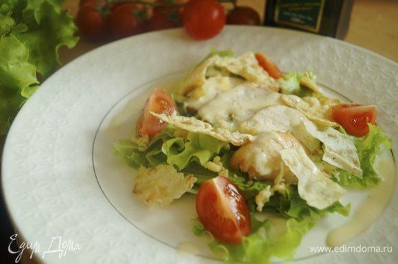 На тарелку, в которой будем подавать салат, выложить листья салата, порванные на крупные части. Затем поместить нарезанное куриное филе, посыпать тертым сыром, полить соусом и выложить помидорки. Чипсы из лаваша выложить на салат непосредственно перед подачей на самый верх, иначе они размокнут.