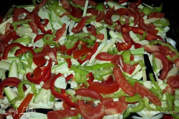 Противень смазываем оливковым маслом и по очереди, выкладываем, равномерно распределяя нарезанные овощи: лук - четверть-кольцами, баклажан, кабачок, перцы и помидоры - соломкой, чеснок - дольками.