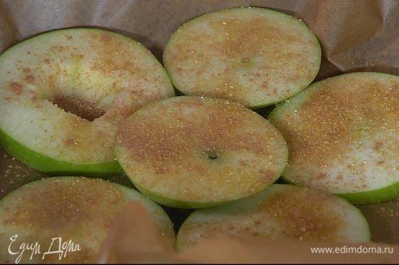 Небольшой противень выстелить бумагой для выпечки, выложить яблочные кольца и посыпать 1/2 ч. ложки сахара и корицей.