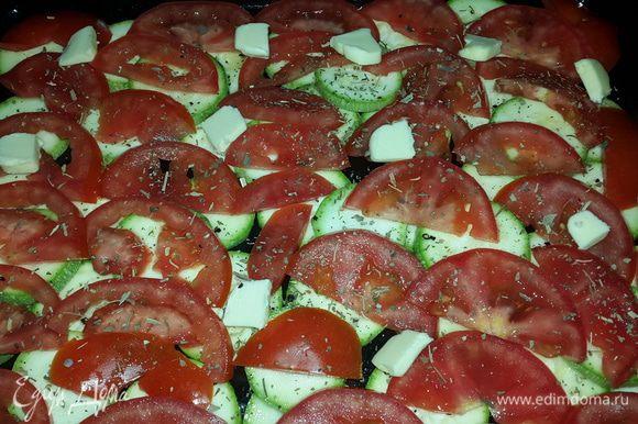 На смазанный оливковым маслом противень выкладываем кабачки, сверху помидоры, немного солим, перчим и посыпаем сушеным базиликом. Раскладываем равномерно кусочки сливочного масла.