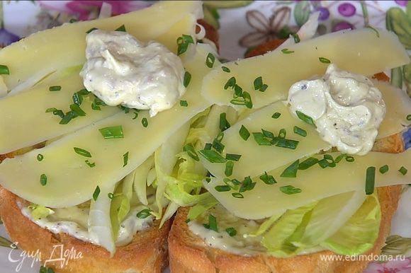 Горячие тосты смазать заправкой, выложить цикорий и сыр, посыпать половиной шнитт-лука и еще раз смазать заправкой.