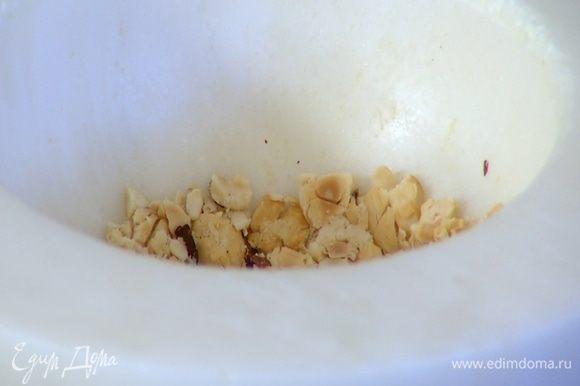 Половину орехов измельчить в ступке в крупную крошку, добавить во взбитые сливки и перемешать.