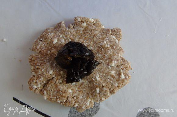 Разделить тесто на шарики (у меня выходит 9 шт), размять в лепешку, посередине положить чернослив, защипнуть и чуть приплюснуть.