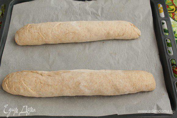 Обминаем и разделим тесто на 2 части. Формируем батоны. Выкладываем на противень, застеленный пергаментом. Накроем полотенцем и ставим в тёплое место на 30 минут.