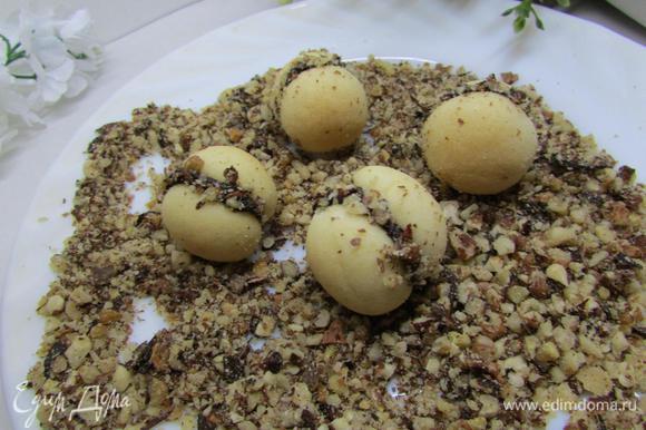 Орехи измельчить в мелкую крошку. Печенье прокатать по орешкам.