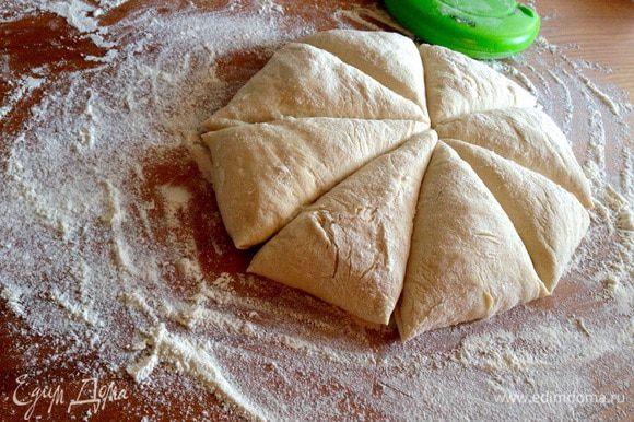 Выложить тесто на густо присыпанную мукой рабочую поверхность, разделить на 8 частей.