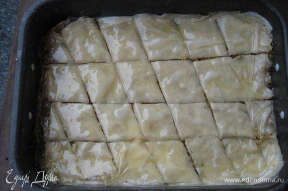 Выложить снова 3-4 слоя фило, каждый слой смазывать сливочным маслом кисточкой, выложить вторую половину орехов. Поверх орехов выложить 3 слоя фило, не забывая смазывать маслом, разрезать пахлаву на ромбики или квадраты не касаясь дна формы.