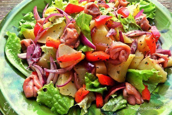Выложить салат на оставшиеся салатные листья, сверху-рыбку.