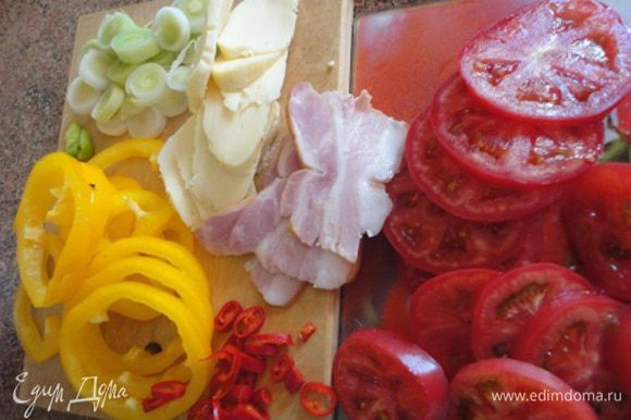 Порей нарезать кружочками. Также очищенные от семян перцы и помидоры. Оливки разрезать вдоль на половинки. Сыр и корейку нарезать ломтиками.