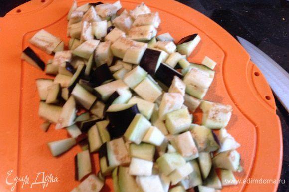 Баклажаны порежьте кубиками, посолите и оставьте на 10 минут, после чего промойте холодной водой и добавьте к луку.