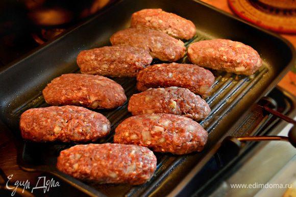 Сковороду-гриль или решётку мангала смажьте слегка маслом и выложите подготовленные колбаски.