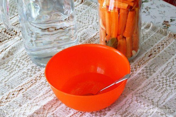 Когда морковка в банке уложена до верха, подготовим маринад. Для этого растворим в мисочке соль, сахар в небольшом количестве воды и добавим уксус.