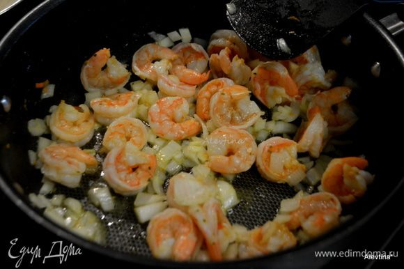 Выложить креветки на горячую сковороду с маслом. Обжаривать 3-4 мин до розового цвета.