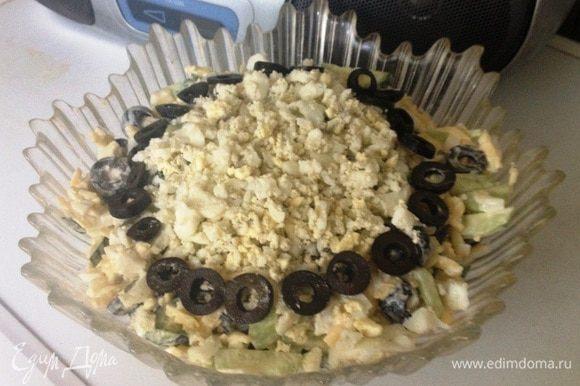 Оставшееся яйцо измельчить. Украсить салат яйцом и колечками маслин. Приятного аппетита!