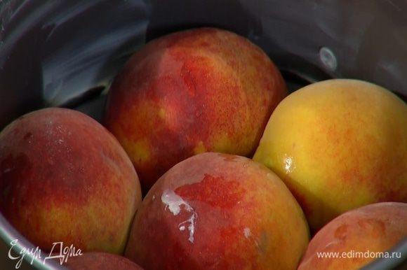Персики разрезать пополам и, удалив косточки, уложить в форму срезами вниз.