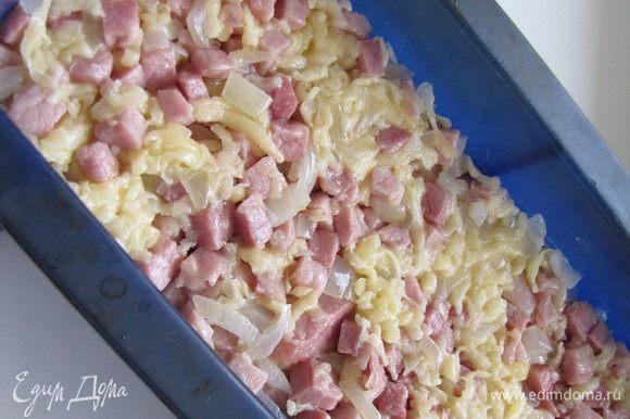 Глубокую форму смазать сливочным маслом (силиконовую можно не смазывать) и выложить ровным слоем половину картофельной смеси. Сверху распределить бекон с сыром и луком.