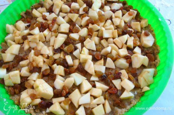 На тесто выложить яблоки и посыпать изюмом.