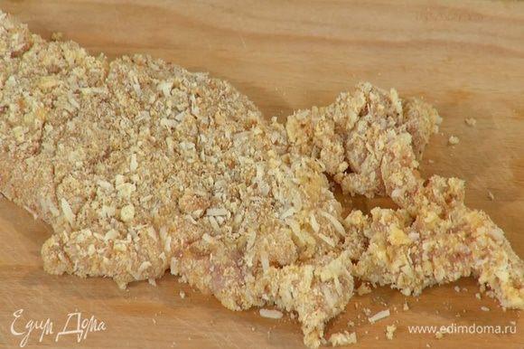 На большую тарелку высыпать муку и обвалять в ней курицу со всех сторон, затем обмакнуть в яйцо и обвалять в сухарях с сыром, стараясь, чтобы панировки на мясе осталось как можно больше.