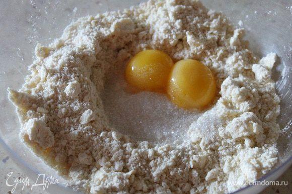 Муку с маслом перетереть руками в крошку. Добавить желтки, воду, сахар и соль.