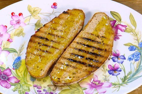 Разогреть сковороду-гриль и подсушить хлеб с двух сторон, затем снять со сковороды и сбрызнуть оливковым маслом.