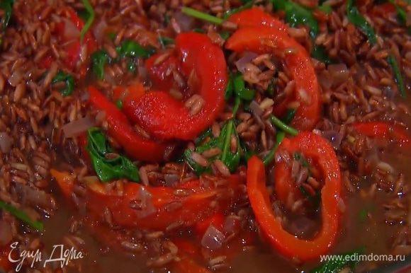 Когда бульон почти весь выкипит, добавить к рису шпинат и сладкий перец, все посолить, поперчить и перемешать. Не накрывая сковороду крышкой, прогревать рис еще некоторое время, пока оставшийся бульон не выпарится.