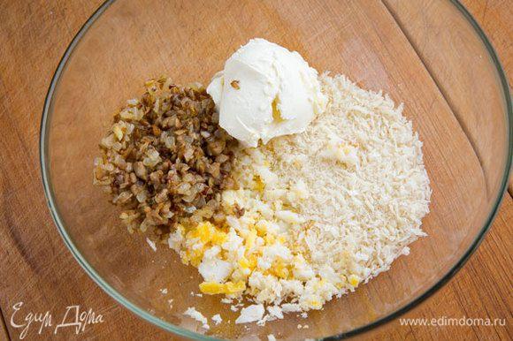 """Твердый сыр потереть на средней терке, а обычный — на крупной. Используйте сыры """"Брест-Литовск"""", с ними такая закуска получится ещё вкуснее! Куриное яйцо сварить, остудить, порезать мелким кубиком. Смешать жареные грибы, яйцо, панировочные сухари, козий сыр."""