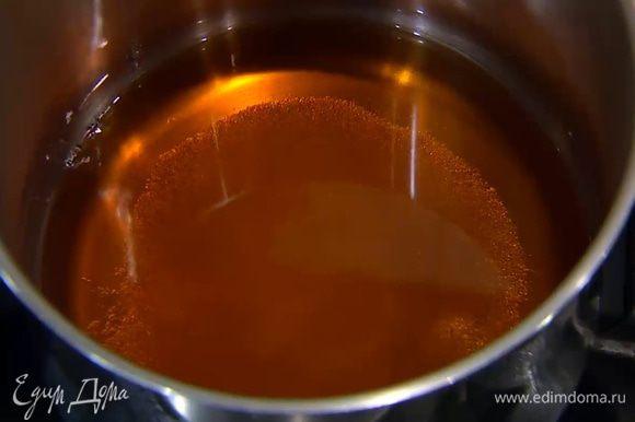 Сахар всыпать в кастрюлю, добавить глюкозу, влить 270 мл теплой воды и на медленном огне сварить сироп.