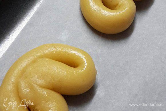 Сворачивать колбаску в форме кренделька и выкладывать на противень.