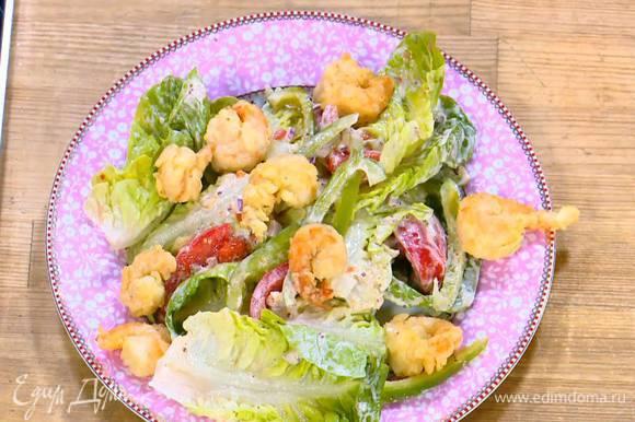 Салат с овощами переложить на блюдо, сверху выложить обжаренные креветки и оставшуюся заправку.