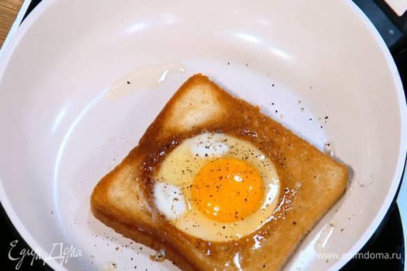 Разогреть в сковороде оливковое масло и обжаривать хлеб с одной стороны до появления золотистой корочки, затем перевернуть, разбить в вырезанные выемки по яйцу, посолить, поперчить и жарить на медленном огне до готовности яиц.