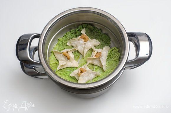 На дно пароварки положить листья салата и поместить решетки с дим сум так, чтобы между ними был промежуток в 2 см. Готовить на сильном огне в течение 7 минут.