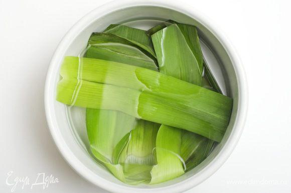От стебля лука порея отделить зеленые листья и на 2-3 минуты опустить их в кипящую подсоленную воду, после хорошо промыть холодной водой (для сохранения цвета).
