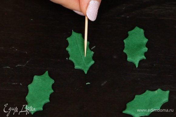 2 вариант — веточки омелы. Из мастики/марципана с помощью формочки вырезаем листики и зубочисткой рисуем прожилки. Если используете мастику, оставьте её немного подсушиться, чтобы листья хорошо держали форму.