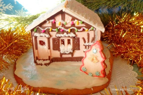 Для подставки раскатать пряничное тесто так, чтобы на него поместился наш домик. Аккуратно перенести домик и залить все белым шоколадом, особенно в местах фундамента. Украсить. Дарить. Радовать детей и взрослых.