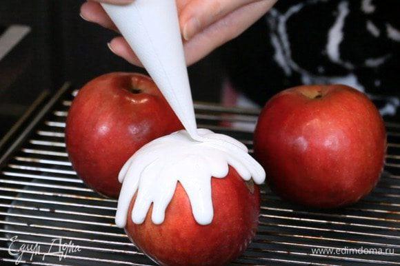На решетку выложить яблоки. Под решётку положить тарелку или постелить плёнку, чтобы лишняя глазурь не попадала на стол. Переложить глазурь в кондитерский мешок. Украсить яблоки. Когда глазурь в кондитерском мешке, легче контролировать аккуратность подтёков.